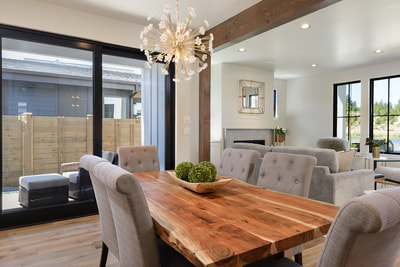 Interior dining room with designer lighting fixture and wood table in Custom home in Bend, Oregon Northwest Crossing built by Structure Development NW an award winning homebuilder in Central Oregon. Farmhouse Style home with stunning interior design.