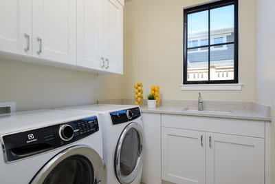 Interior laundry room with white appliances and cabinets in Custom home in Bend, Oregon Northwest Crossing built by Structure Development NW an award winning homebuilder in Central Oregon. Farmhouse Style home with stunning interior design.